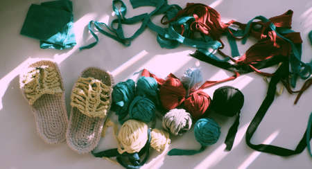 Top view colorful scene in sunlight morning, ball of yarn from recycle old t shirt on white background, fun leisure with homemade reuse by cut clothes in yarns