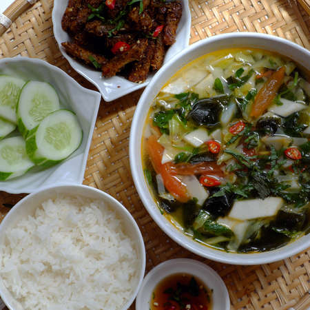 Top view tray of Vietnamese meal for lunch on white background, vegetarian homemade food with seitan fried with citronella, chili, bowl  of vegetable soup and rice dish, simple cuisine from vegetal