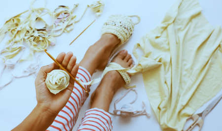 Top view leisure activity to make handmade sandals from old T shirt, Vietnamese woman recycle by cut clothes to make yarn ball then crochet, human foot diy thongs on white background 版權商用圖片