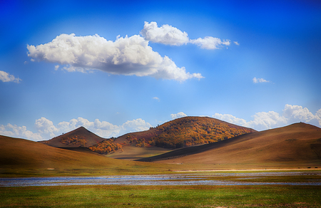 Autumn scenery of Inner Mongolia grassland, rolling hills and blue sky and white clouds Stock fotó