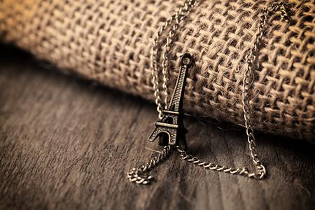 Eiffel tower necklace on sackcloth background Zdjęcie Seryjne