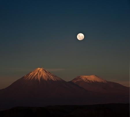 Full-moon in the Moon Valley  Volcanoes Licancabur and Juriques, west of San Pedro de Atacama, Chile in the Cordillera de la Sal, in the Atacama desert of Chile