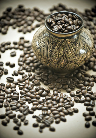 Coffee from the South America  Coffee grains in the jug made by Indians and ornamented manually photo