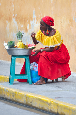 CARTAGENA, MAY 13  Palenquera woman with typical dress sells fruit on the Street on May 13, 2010 in Cartagena, Colombia  Palenqueras are a unique african ethnic group in the north of South America
