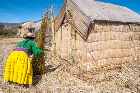 national costume: Unrecognizable woman in national costume Indian Uros knits a sheaf  Uros - Floating Islands, Titicaca, Peru Stock Photo