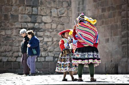 quechua: CUZCO, PERU, AUGUST 1 - Quechua Indians break from posing with tourists, drinking sodas - August 1, 2011 in Cuzco, Peru