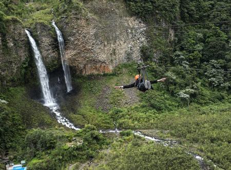 Tourist gliding on the zip line trip against Bridal veil (Manto de la novia), waterfall in Cascades route, Banos, Ecuador Standard-Bild