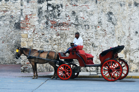 afro caribbean ethnicity: CARTAGENA, MAY 12: Horse drawn touristic carriages waiting alongside the fortified walls of the historic Spanish colonial city of Cartagena de Indias in Colombia