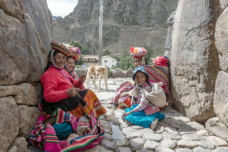 pisaq: Ollantaytambo, Peru - december 18, 2014: Women and children in traditional Peruvian clothes break from posing with tourists in Ollantaytambo, Peru