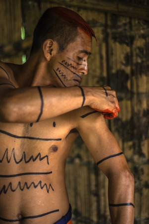 grease paint: SANTO DOMINGO, ECUADOR - JANUARY 26, 2015: Indian man Colorados (Los Tsáchila) tribe in national clothes paints hair juice plants achiote for ritual purposes, on January 26, 2015 in Santo Domingo, Los Rios, Ecuador