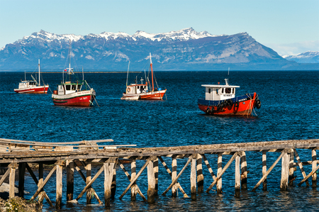 Puerto Natales, Chile - April 21, 2011: Colourful wooden fishing boats in the harbour at Puerto Natales port Editorial