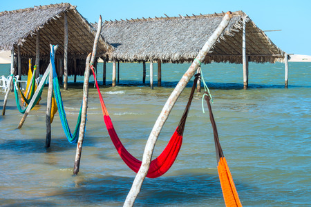 sun roof: Hammocks and beach chairs under the shade of a palapa sun roof umbrella in Jericoacoara, Brazil Stock Photo