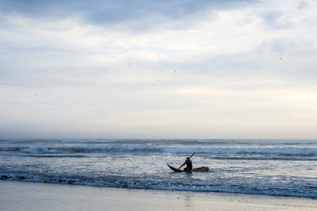 Pimentel, Peru - March 15, 2015: The fisherman goes to sea on a Traditional Peruvian small Reed Boats (Caballitos de Totora), straw boats still used by local peoples in Peru