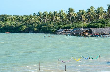 Jericoacoara, Ceara state, Brazil - July 2016: tourists and hammocks are on the beach and Lagoon Tatajuba from above