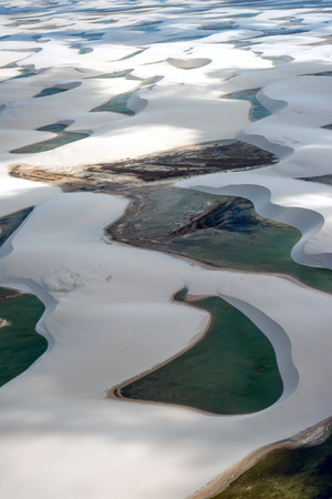 Aerial view of Lencois Maranhenses National Park, Brazil, low, flat, flooded land, overlaid with large, discrete sand dunes with blue and green lagoons