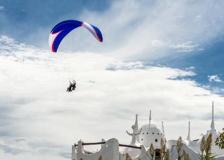 Punta del Este, the Atlantic Coast, Uruguay - Mar�h 23, 2013: Paraglider  flies over the Casapueblo Hous, the combination studio, home, museum and hotel designed and built by, and belonging to the artist, Carlos Paez Vilaro