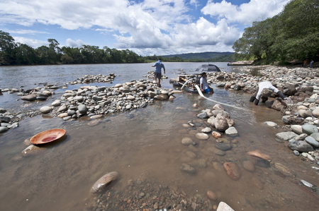 Misahualli, Napo Province, Ecuador - December 27, 2010: Local Indians People panning for Gold with wood batea (Spanish for