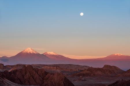 Full-moon in the Moon Valley. Volcanoes Licancabur and Juriques, west of San Pedro de Atacama, Chile in the Cordillera de la Sal, in the Atacama desert of Chile