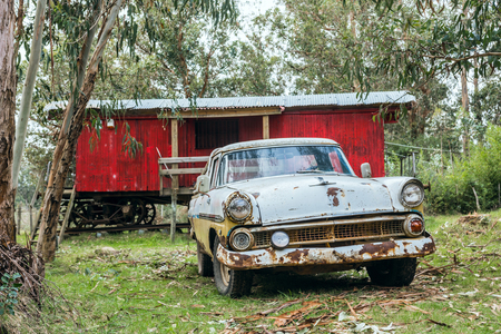 Punta Negra, Maldonado province, Uruguay - June 29, 2017: Rusty old car parked in front of an old Railroad boxcar transformed into a small house Stock Photo