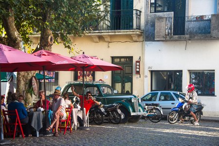 Colonia del Sacramento, Uruguay - April 5, 2013:  Tourists enjoy a sunny autumn day in a street cafe in the historic center of one of the oldest towns in Uruguay