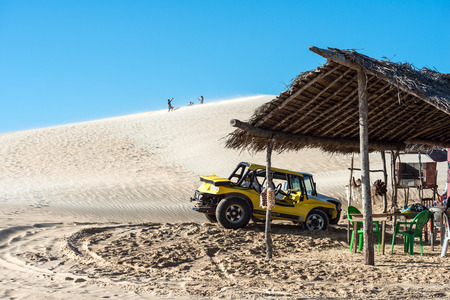 Jericoacoara, Ceara state, Brazil - July 17, 2016: Buggy and moto with tourists traveling through the desert Jericoacoara National Park Editorial