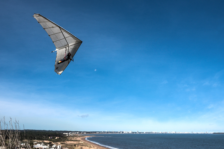 Punta del Este, the Atlantic Coast, Uruguay - August 2, 2017: Hang-glider flies over the Punta Ballena cape, against the background of the resort city of Punta del Este on the horizon Editorial