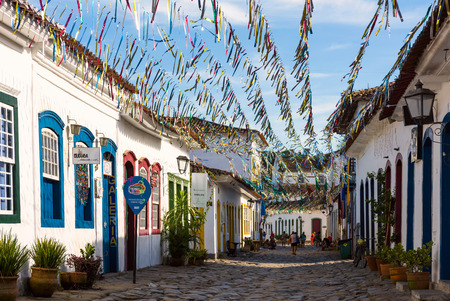 Paraty, Brazil - February 24, 2017: Typical cobblestone street with colonial buildings in historic town Paraty on the time of Carnival, Brazil
