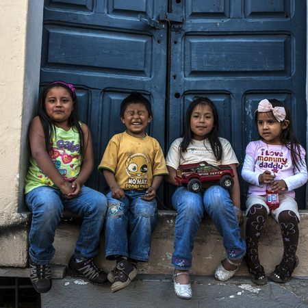 Quito, Ecuador - May 27, 2012: Happy Indigenous children sitting on the doorstep of a house in the historic center of Quito and smiling at the camera
