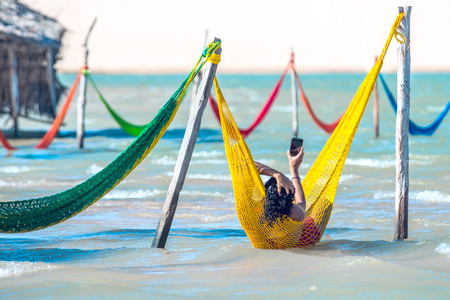 Jericoacoara, Brazil - July 17, 2016: Woman relaxing on hammock and do selfie on vacation