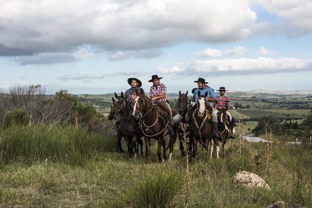 Minas, Uruguay: Marth 30, 2017 - The gauchos ride from one cattle pasture to another, along the road to Minas, Maldonado Department Editorial