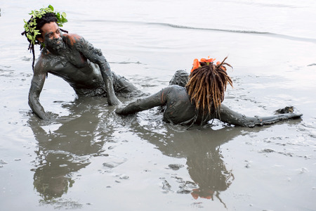 Paraty, Rio de Janeiro State, Brazil – February 25, 2017: Clad in swimwear and rags, slathered in mud, adorned with branches and bones and crying