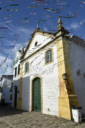 Paraty, Brazil - February 24, 2017: Typical cobblestone street with colonial buildings in historic town Paraty on the time of Carnival, Brazil Standard-Bild - 103491456