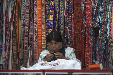 Otavalo, Ecuador - July 5, 2012: Indian women in national clothes sells the products of her weaving, as usual on weekdays on the most famous markets in South America, on August 4, 2012 in Otavalo, Ecuador