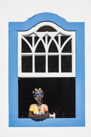 Paraty, Brazil - February 28, 2017: Traditional brazilian souvenir girl at the country house window in historic town Paraty, Rio de Janeiro state, Brazil