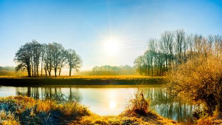 Landschaft mit Fluss bei Sonnenaufgang