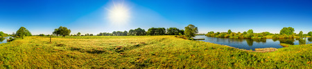 Landscape in summer with trees, meadows, river and sun Stok Fotoğraf