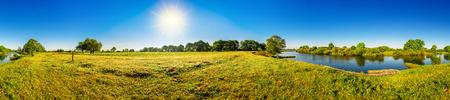 Landschap in de zomer met bomen, weiden, rivier en zon