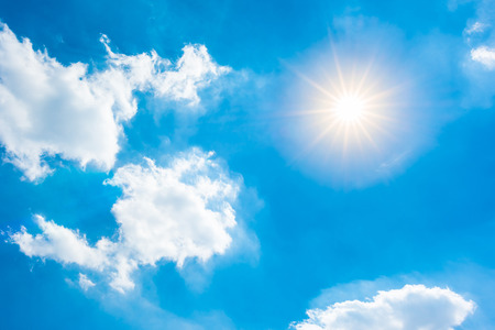 Sunny background, blue sky with white clouds and bright sun Stock Photo