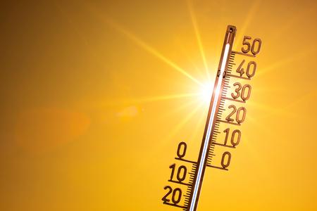 Heißer Sommer oder Hitzewellenhintergrund, helle Sonne mit Thermometer