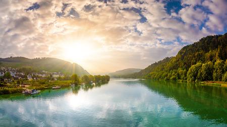 Amanecer en el río con montañas y bosques de fondo