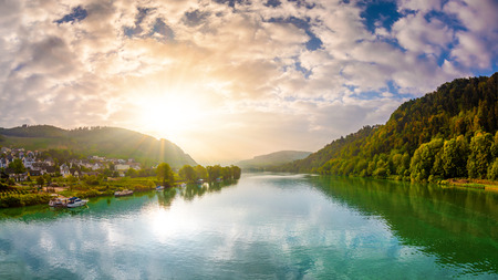 Sunrise at the river with mountains and forest in the background