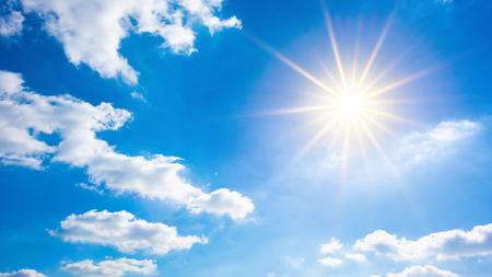 Heißer Sommer- oder Hitzewellenhintergrund, schöner blauer Himmel mit glühender Sonne und weißen Wolken Standard-Bild