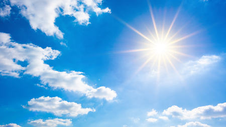 Hete zomer of hittegolf achtergrond, mooie blauwe lucht met gloeiende zon en witte wolken Stockfoto