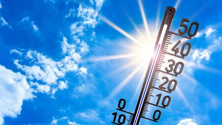 Hot summer or heat wave background, bright sun on blue sky with thermometer