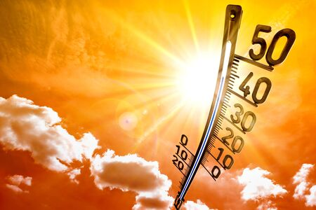 Hot summer or heat wave background, glowing on orange sky with thermometer Stockfoto