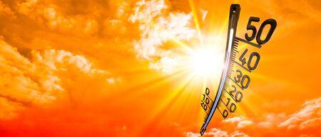 Heißer Sommer- oder Hitzewellenhintergrund, glühend am orangefarbenen Himmel mit Thermometer Standard-Bild