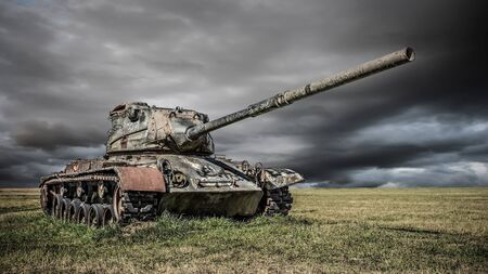 Old battle tank on a field Stock Photo
