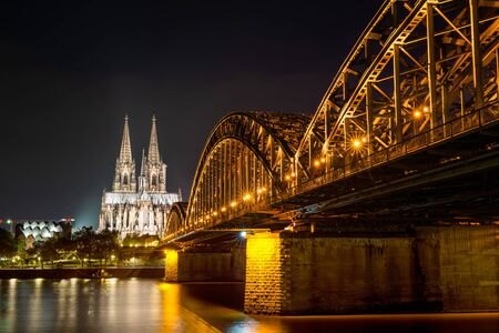 The Hohenzollern Bridge over the Rhine River and Cologne Cathedral by night