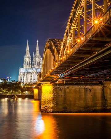 The Hohenzollern Bridge over the Rhine River and Cologne Cathedral by night Stock Photo - 137131517