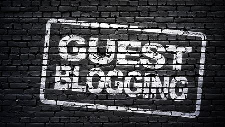 Guest blogging sign, white text on black brick wall